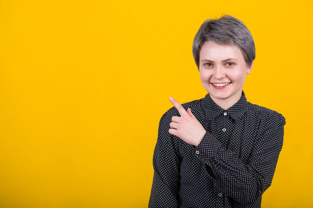 Beautiful young woman hipster, short hairstyle, pointing forefinger away, looking with joyful face expression to camera, wears black shirt, isolated over yellow background with copy space.