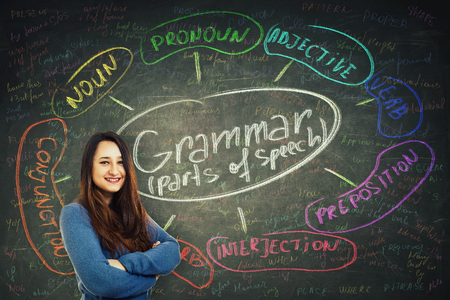 Pretty casual woman teacher smiling and holding arms crossed over blackboard background chalk written english grammar parts of speech. Opportunity to study system and structure of a language. 免版税图像