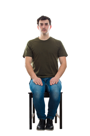 Full length portrait of casual young man sitting on a chair, hands on knees, looking serious to camera isolated over white background.