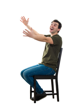 Side view full length portrait of excited casual young man seated on a chair keeps arms outstretched for hug like greeting an old friend isolated over white background with copy space.