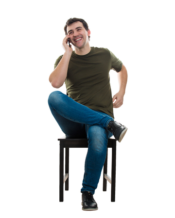 Full length portrait, cheerful casual young man seated on a chair smiling while talking on mobile phone isolated over white background. Happy relaxed young guy speaking on telephone receive good news.