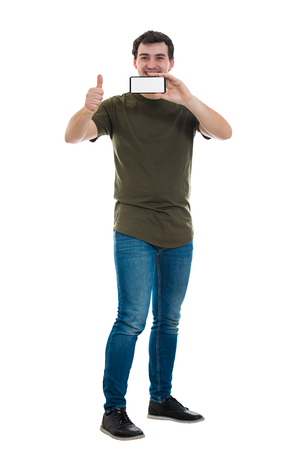 Handsome casual guy presenting a trendy mobile phone with blank screen copy space for ads. Positive smiling man recommending a new smartphone and thumb up gesture isolated over white background. Stockfoto
