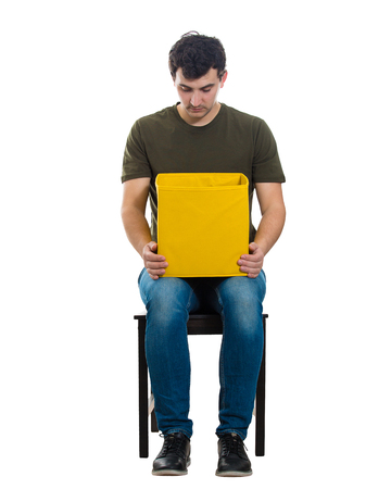 Full length portrait of a curious casual guy sitting on a chair looking inside a yellow box isolated over white background. Stock Photo