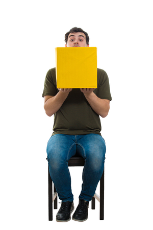 Full length portrait of a curious casual guy sitting on a chair looking cautious inside a mysterious yellow box isolated over white background. Stock Photo