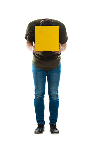 Full length portrait of a curious casual guy sitting puts his head inside a magic yellow box looking cautious for what's inside isolated over white background.