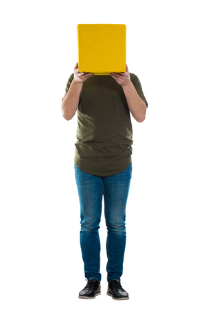 Full length portrait of casual incognito young man holding a yellow box instead head isolated over white. Introvert people hiding faces behind mask. Social issue fake identity concept.