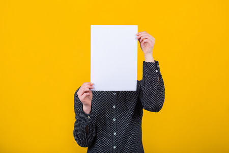Businesswoman covering her face using a blank white paper sheet, like a mask for hiding her identity isolated over yellow wall background. Introvert female anonymity concept.