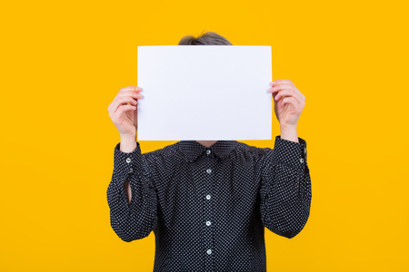 Woman covering her face using a blank white paper sheet, like a mask for hiding her identity isolated over yellow wall background. Introvert female anonymity concept.