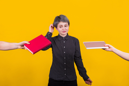 Puzzled young woman student choosing a traditional textbook instead modern ebook as two hands give her reading choice options. Education concept, doubtful reader make choice isolated over yellow wall.