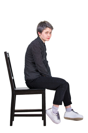 Side view full length portrait of tired young woman seated on a chair looking disappointed to camera isolated over white background.
