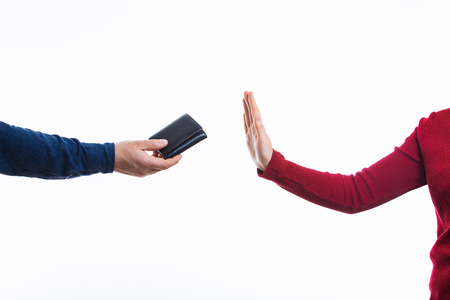 A man hand holding wallet and female hand rejecting to receive money over white background. Conceptual stop corruption. Corruption reject concept.