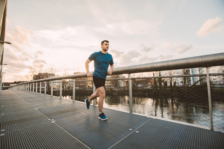 Fitness, sport, healthy lifestyle concept. Young athlete running over bridge in sunset light. Healthy lifestyle concept.