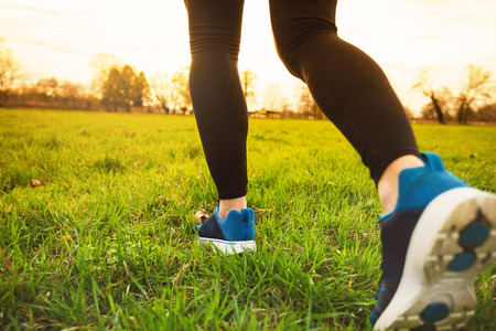 Runner athlete feet running on grass.Male fitness sunlight jogging workout. Sport athlete active lifestyle concept.Athletic pair of legs running on grass during sunset city park.