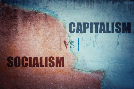 Socialism versus capitalism split concrete wall cracked in two different halves, red and blue side. Socialist centralized economic planning vs capitalist liberated free market. Future strategy choice. Stock Photo