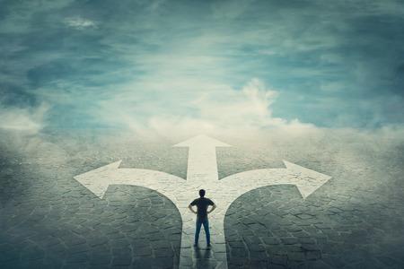 Un homme confiant, les mains sur les hanches, se tient devant un carrefour avec une route divisée de trois manières différentes sous forme de flèches. Choisir le bon chemin entre la gauche, la droite et l'avant. Concept de décision difficile.