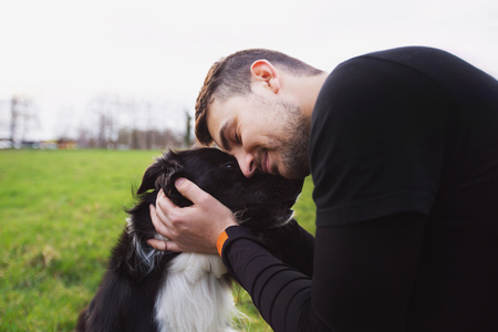 Man embracing his border collie dog . Young owner hugs his pet. Friendship between owner and dog. Animal love concept.