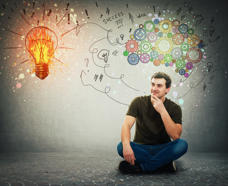 Cheerful man sitting on the floor smiling looking at a bright light bulb on the wall. Idea concept, positive thinking as colorful gear brain above head, create a genius. Mental development symbol.