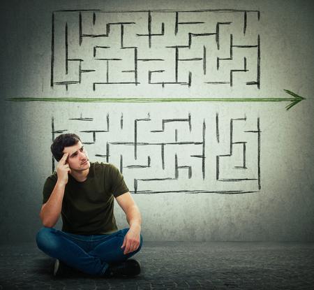 Hombre sentado en el suelo pensando mucho, encontrar una solución para resolver el problema y escapar del laberinto. Rompiendo las reglas, mientras una flecha verde atraviesa las paredes del laberinto. Imaginación diferente, idea alternativa.