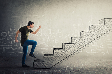 Motivated and confident young man hurry to climb a imaginative staircase. Concept of career development, success and goal achievement. Casual guy rush, making a big step.