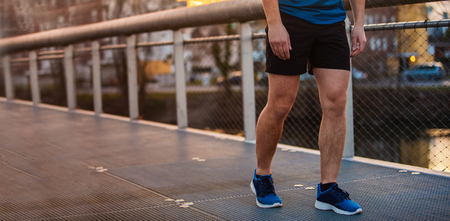 Close up of young man sporty legs running outdoor along a bridge in the morning. Self overcome conquering obstacles and win. Healthy lifestyle concept. Workout jogging activity, dynamic runner athlete