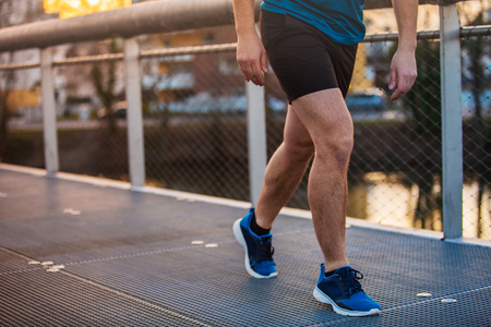 Close up of young man sporty legs running outdoor along a bridge in the morning. Self overcome conquering obstacles and win. Healthy lifestyle concept. Workout jogging activity, dynamic runner athlete.