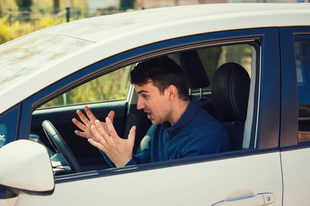 Angry man driving a vehicle arguing and gesturing shaking his hands perplexed. Irritated and furious guy negative facial expression, while driving the car waiting in a traffic jam. Stock Photo