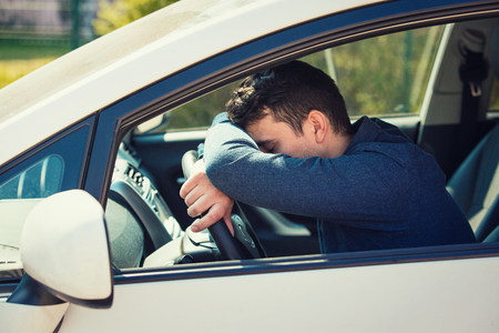 Un homme décontracté presque endormi garde la main et la tête sur le volant, fatigué d'attendre dans les embouteillages après le travail à l'heure de pointe. Un jeune homme épuisé arrête de conduire sa voiture pour se reposer.