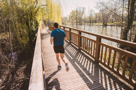 Rear view Male runner running in a city park over bridge training for fitness. Healthy lifestyle concept. Workout jogging activity, dynamic runner athlete. Stock Photo