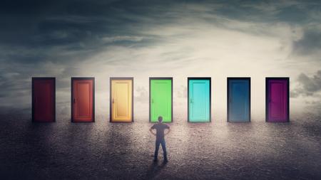 Selbstbewusster Kerl vor vielen verschiedenfarbigen Türen muss sich für eine entscheiden. Schwierige Entscheidung, wichtiges Wahlkonzept, Misserfolg oder Erfolg. Wege in eine unbekannte Zukunft, Karriereentwicklungsmöglichkeit.