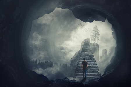 Surreal view as a man escape from a dark cave climbing a mystic stairway crossing the misty abyss going up to unknown paradise. Opportunity staircase, exit way to success, freedom concept. Archivio Fotografico