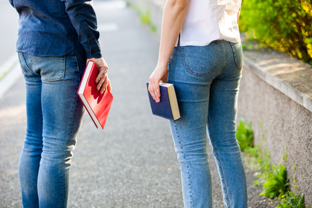 University. Rear view of students holding books looking to university. Approved young smiling student in the University of his dream. Rear view students on campus with books in their hands.