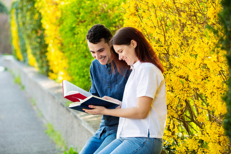 Students learning for exam together in a city park. Students Brainstorming Meeting  learning for exam. Fast learning concept. Students Teamwork. Stock Photo