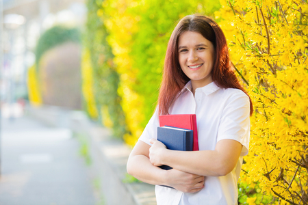 Smiling portrait of female university student outdoors on Campus holding books looking to camera. A confident student holding books over university building background.