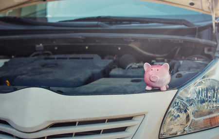 Pink piggy money box on the opened hood of a broken car. Financial credit for transportation repair services. Vehicle breakdown and investitions concept. Automobile insurance.
