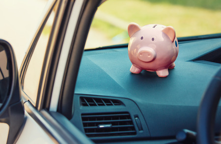 Pink piggy money box inside a car transportation. Saving money for vehicle purchase. Successful financial planning and banking concept. Economic investment for future. Buy or loan automobile. Banco de Imagens