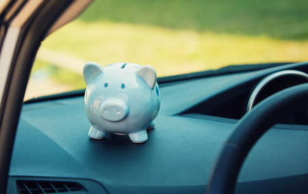 Piggy money box inside a car transportation. Saving money for vehicle purchase. Successful financial planning and banking concept. Economic investment for future. Dealership offering credits. Banco de Imagens
