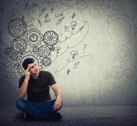 L'uomo seduto sul pavimento pensa intensamente, trova una soluzione per risolvere il problema. Immaginazione diversa, idea alternativa. Frecce cerebrali dell'ingranaggio e disordine come pensieri. Concetto per lo sviluppo mentale e psicologico