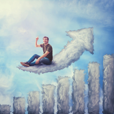 Fantasy concept as an excited guy seated on a cloud shaped as increasing graph, looking and pointing index finger up, dreaming of life success isolated against blue sky background.