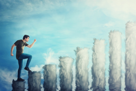Fantasy concept as a confident guy stepping on a staircase as a graph made of clouds. Man going up hurried over a blue sky background. Growing success concept, business metaphor.