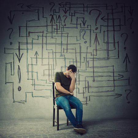 Pessimistic, disappointed man sitting on a chair in a dark room covering face with hand. Desperate guy try to solve a questions maze and find the correct answer. Problem analysis solution concept.