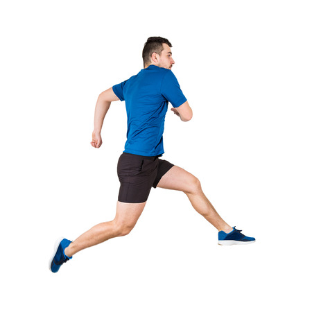 Side vie full length of determined caucasian man athlete jumping over imaginary obstacle isolated over white background. Young guy runner wearing black and blue sportswear makes a leap over chasm. Stock Photo