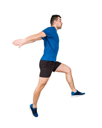 Side vie full length of determined caucasian man athlete jumping over imaginary obstacle isolated on white background. Young guy runner wearing black and blue sportswear makes a leap over chasm. Stock Photo