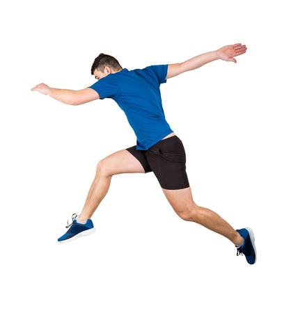 Side vie full length of determined man athlete jumping over imaginary obstacle isolated over white background. Young guy runner in sportswear makes sprint for leap over chasm. Stock Photo