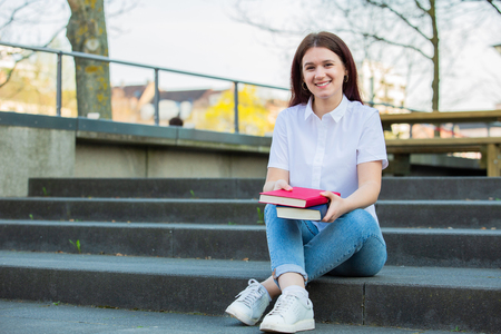 Smiling portrait of female university student sitting down on Campus stairs holding books looking to camera. Confident student smiling and holding books on university background.