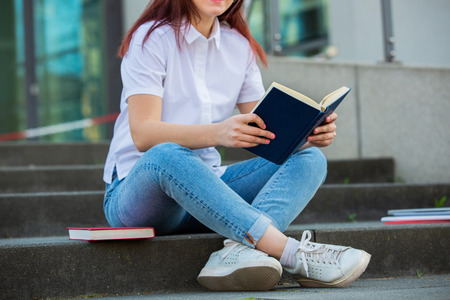 University student outdoors on Campus sitting on stairs holding books. A confident student holding books over university building background learning for an exam.