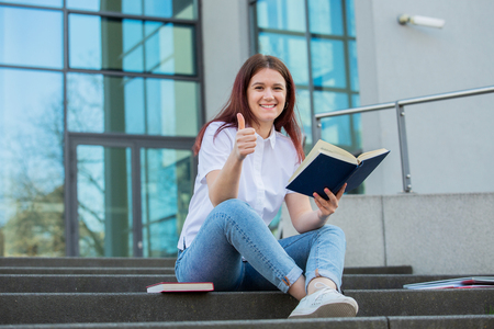 Smiling university student with thumb up gesture outdoors on Campus sitting on stairs holding books. A confident student holding books over university building background learning for an exam.