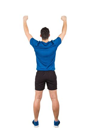 Rear view full length of young man athlete with hands raised, celebrating victory. Self overcome concept, achieving success. Sporty guy wearing sportswear honor his win isolated over white background.