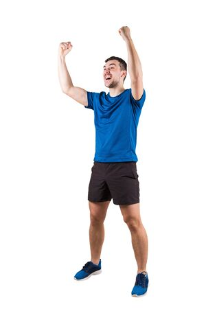 Full length portrait of young man athlete with hands raised, celebrating victory. Self overcome concept, achieving success. Sporty guy wearing sportswear honor his win isolated over white background.