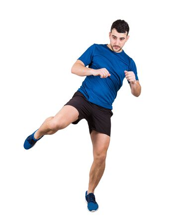 Full length portrait of young man athlete or fighter making a leg kick isolated over white background. Sporty caucasian guy boxer training. Stock Photo