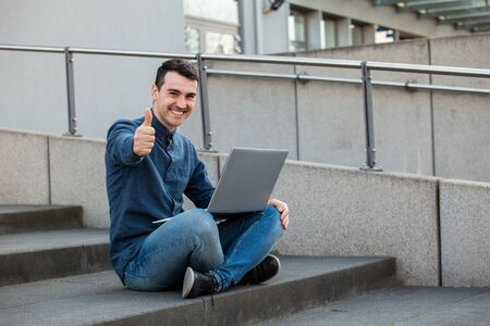 Smiling happy man with thumb up gesture and  laptop on knees, seated on a stairs celebrating success. Freelancer guy with thumb up working at his notebook computer, full length.